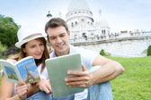 Casal usando tablet em frente a basílica de sacré coeur — Foto Stock