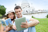 Couple using tablet in front of Sacre Coeur Basilica — Stok fotoğraf
