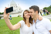 Lovers taking picture of themselves in front of Sacre Coeur — Stock Photo