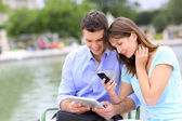 Couple using tablet and cellphone in public park — Stok fotoğraf