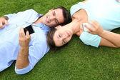 Par avkopplande i gräset medan du använder smartphone — Stockfoto