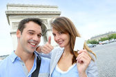 Cheerful couple holding tourist ticket by the Arch of Triumph — Stock Photo