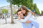 Man giving piggyback ride to girlfriend on the Champs Elysees — Stock Photo