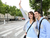 Couple of tourists in Paris calling for a taxi cab — Stock Photo
