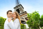 Couple embracing each other in front of the Eiffel tower — Stok fotoğraf