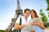 Turistas usando tableta electrónica frente a la torre eiffel — Foto de Stock
