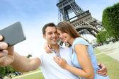 Pareja en parís tomando fotos frente a torre eiffel — Foto de Stock