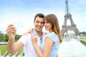 Couple in Paris taking pictures in front of Eiffel Tower — Stock Photo