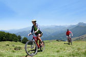 Couple riding bicycles in the mountains — Stock Photo
