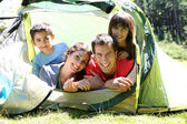 Portrait of family laying in camp tent — Stock Photo