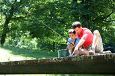 Father fishing with son on a bridge in the mountain — Stock Photo