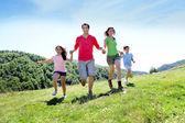 Glad familj njuter och kör tillsammans i bergen — Stockfoto