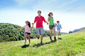 Happy family enjoying and running together in the mountains — Stok fotoğraf