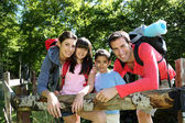 Family on a hiking day resting along fence — Foto Stock