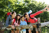 Family on a hiking day resting along fence — Stock Photo