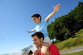 Daddy carrying son on his shoulders — Stock Photo