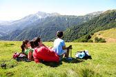 Family laying down the grass enjoying mountain view — Stock Photo
