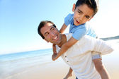 Father holding son on his shoulders at the beach — Stock Photo