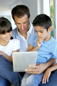Father and kids websurfing on digital tablet — Stock Photo