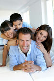 Portrait of happy family laying down bed — Stock Photo