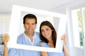 Closeup of cheerful couple looking through frame — Stock Photo