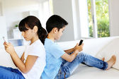 Kids playing at home with smartphones — Stock Photo
