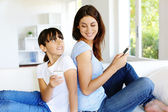 Mother and daughter using mobile phone at home — Stock Photo