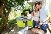 Family cooking meat on barbecue grill — Stok fotoğraf