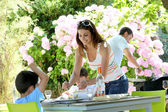 Mother serving lunch to kids in home garden — ストック写真