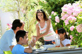 Woman serving water to family having lunch — Stock Photo
