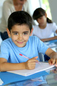 Portrait of smilng young boy sitting in classroom — Stock Photo