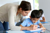 учитель помогает молодым мальчиком с написания урок — Стоковое фото