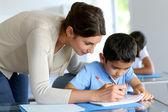 Insegnante aiutare il giovane ragazzo con lezione di scrittura — Foto Stock