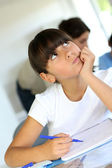 Closeup of schoolgirl in class with thoughtful look — Stock Photo
