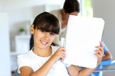 Closeup of beautiful school girl showing notebook page — Stock Photo