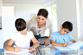 Teacher and kids in classroom writing on notebook — Stock Photo
