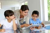Kobieta nauczania klasa do dzieci w wieku szkolnym z cyfrowy tablicowy — Zdjęcie stockowe