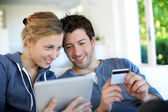 Happy young couple doing shopping on internet — Stock Photo