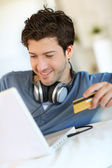 Young man buying music on internet with tablet — Stock Photo