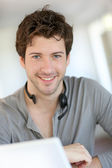 Student at home working with laptop and headset — Stock Photo
