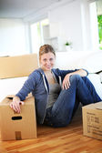 Young girl sitting by cardboards in new home — Stockfoto