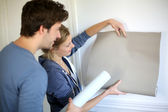 Young couple choosing color of all paper in new home — Stock Photo