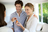 Happy young couple getting keys of their new home — Stock Photo