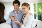 快乐的年轻夫妇,让他们的新家的钥匙 — 图库照片