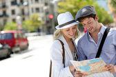Moda joven pareja en la ciudad con el mapa turístico — Stockfoto