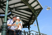 Young couple standing in gazebo reading touristic map — Foto de Stock