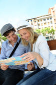 Young couple sitting on public bench to read touristic map — Foto de Stock