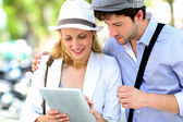 Young couple in town using electronic tablet — Stock Photo