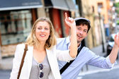 Young couple hailing for a taxi cab — Stock Photo