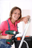 Woman standing on scale with electric drill — Stock Photo